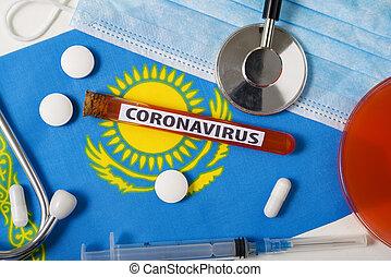 Coronavirus, nCoV concept. Top view protective breathing mask, stethoscope, syringe, tablets on the flag of Kazakhstan.