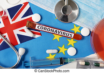 Coronavirus, nCoV concept. Top view protective breathing mask, stethoscope, syringe, tablets on the flag of Tuvalu.