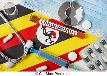 Coronavirus, nCoV concept. Top view protective breathing mask, stethoscope, syringe, tablets on the flag of Uganda.
