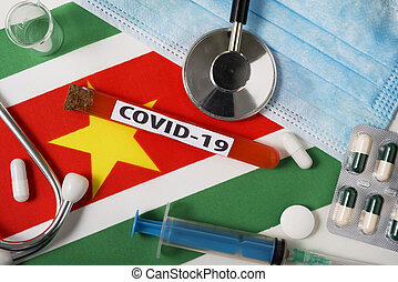 Coronavirus, the concept COVid-19. Top view protective breathing mask, stethoscope, syringe, tablets on the flag of Suriname.