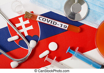 Coronavirus, the concept COVid-19. Top view protective breathing mask, stethoscope, syringe, tablets on the flag of Slovakia.