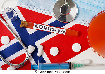Coronavirus, the concept COVid-19. Top view protective breathing mask, stethoscope, syringe, tablets on the flag of Norway.