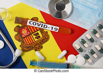 Coronavirus, the concept COVid-19. Top view protective breathing mask, stethoscope, syringe, tablets on the flag of Andorra.