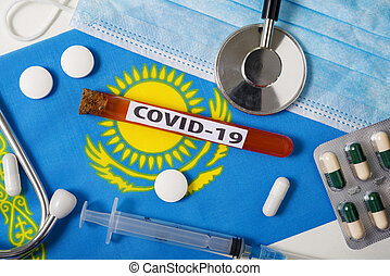 Coronavirus, the concept COVid-19. Top view protective breathing mask, stethoscope, syringe, tablets on the flag of Kazakhstan.