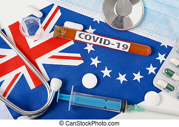 Coronavirus, the concept COVid-19. Top view protective breathing mask, stethoscope, syringe, tablets on the flag of the cook Islands.