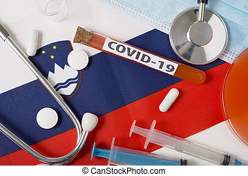 Coronavirus, the concept COVid-19. Top view protective breathing mask, stethoscope, syringe, tablets on the flag of Slovenia.