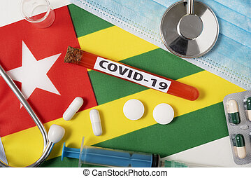 Coronavirus, the concept COVid-19. Top view protective breathing mask, stethoscope, syringe, tablets on the flag of Togo.