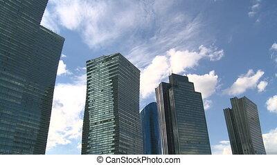 Corporate buildings on blue cloudy sky. timelapse