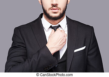 Corporate confidence meets exceptional style. Cropped image of fashionable young man adjusting his necktie while standing against grey background