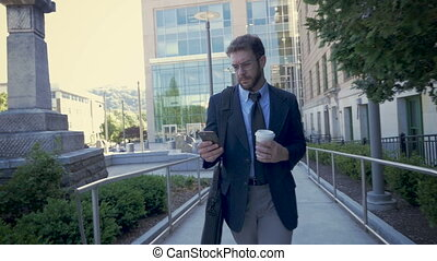 Corporate executive leaving his urban office walking and using mobile device