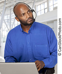 Corporate looking African businessman looking serious while conversing on his voip headset and working on his laptop computer.