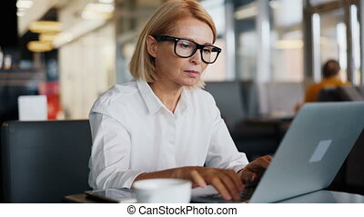 Corporate manager mature lady working with laptop in cafe...