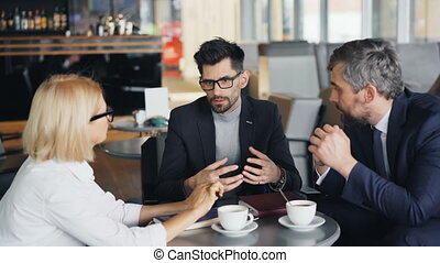 Corporate managers mature businesspeople talking in cafe discussing work