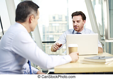 two caucasian business men having a conversation in office.