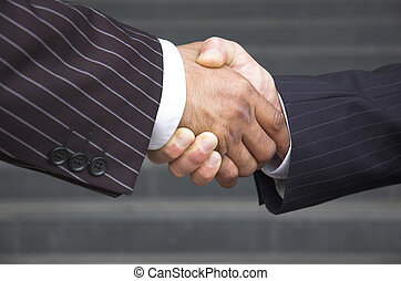 Corporate trust - Businessmen in pinstripe suits shake hands...