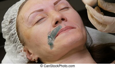 Correction or waxing. Green warm wax is applied to the woman...