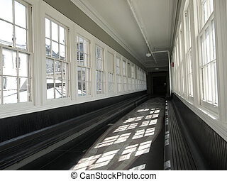 Corridor - long old corridor with wooden benches on both...