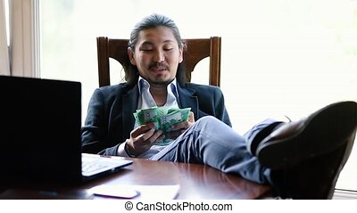 Corrupt businessman counting his earnings with a greedy look on his face