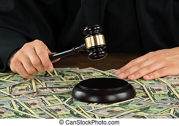 Corrupt Judge Hitting Gavel With Banknotes Spread At Desk