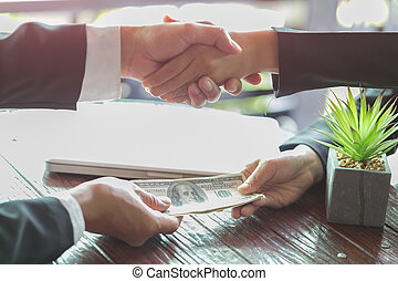 Corrupted businessman sealing the deal with a handshake and receiving a bribe money, anti bribery and corruption concepts
