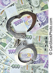 Corruption - Police handcuffs on Czech banknotes, czech crown money CZK - the concept of finance and crime