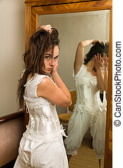 Woman in victorian underwear bloomers and lace corset looking in an antique mirror