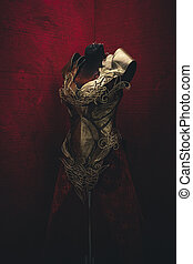 Corset Golden armor for women. Carries pieces of gold and fabrics and feathers in red color