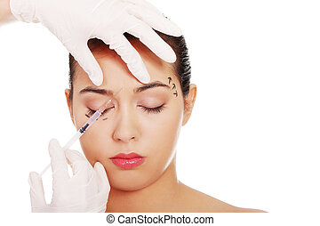 Cosmetic botox injection in the female face, eye and eyebrow...