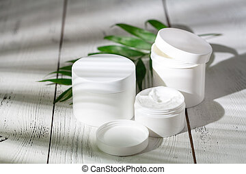 Cosmetic bottle containers with green herbal leaves, Blank label package for branding mock-up, Natural organic beauty product concept