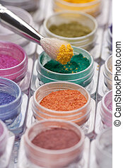 cosmetic brush pigment above containers of pigments - a ...