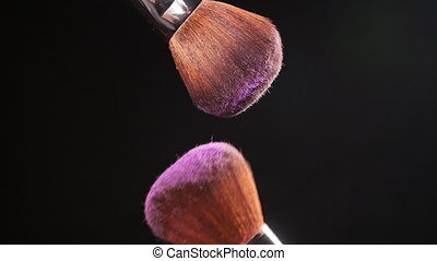 Cosmetic brush with pink cosmetic powder on black background