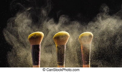 Cosmetic brushes with golden cosmetic powder on black...