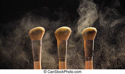 Cosmetic brushes with golden cosmetic powder on black background