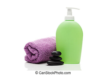 cosmetic containers, towel and black spa stones isolated on white