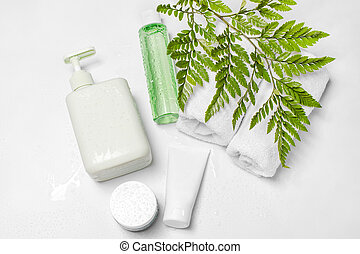 Cosmetic containers with green herbal leaves and water drops, blank label package for branding mock-up. Moisturizing cream, shampoo, tonic, face and body skin care. Natural organic beauty product