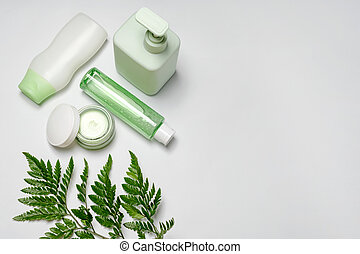 Cosmetic containers with green herbal leaves, blank label package for branding mock-up. Moisturizing cream, shampoo, tonic, face and body skin care. Natural organic beauty product. Flat lay, top view.