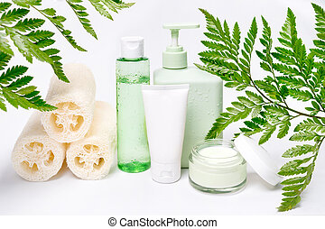 Cosmetic containers with green herbal leaves, blank label package for branding mock-up. Moisturizing cream, shampoo, tonic, face and body skin care. Natural organic beauty products.