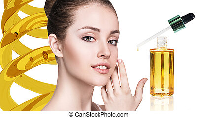Cosmetic oil applying on face of young woman.