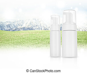 Cosmetic product for cream, foam, shampoo. on Panorama of Mountain Snow Landscape with green grass .