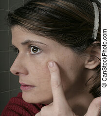 cosmetic spot - profile view of woman looking at her skin