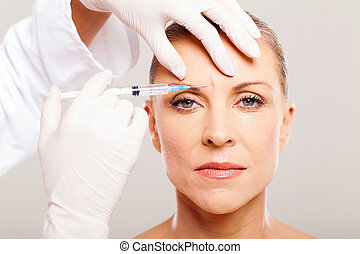 cosmetic surgeon giving face lifting injection to mature...