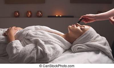 cosmetician, aan het dienen, gezichtsmasker, om te, de, gezicht, van, jonge vrouw , in, spa, salon.