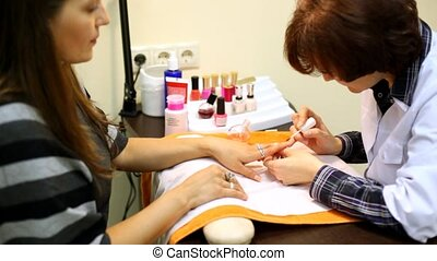 Cosmetician accurately covers nails of client with transparent nail polish