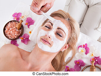 Cosmetician Applying Facial Mask On Face Of Woman -...