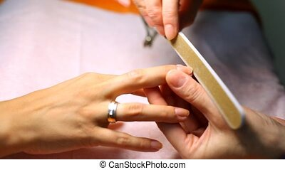 Cosmetician does manicure and saws nails of client file for nails