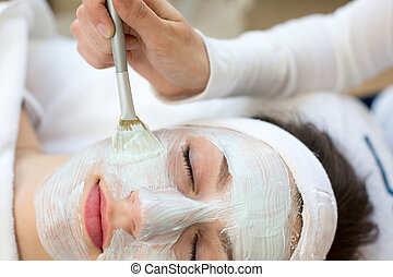Cosmetician giving client facial skincare mask - Cosmetician...