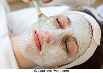 Cosmetician applying facial skincare mask to customer