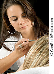 Cosmetician - Beautician applying eye make-up to a young...