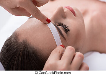 Cosmetician undergoing waxing procedure for human brow -...