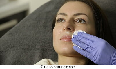 cosmetician wipes face of female patient with cotton Sponge...